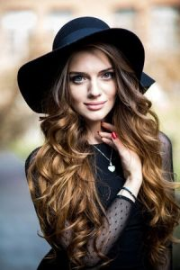 curly festival hair with hat at Synergy hair & Beauty Salon in Studley